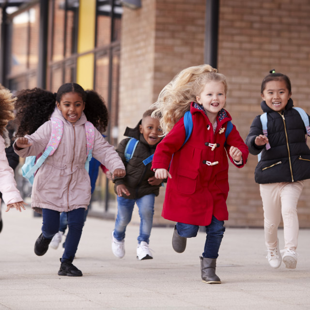 """""""Happy young school girls wearing coats and carrying schoolbags running in a..."""" stock image"""