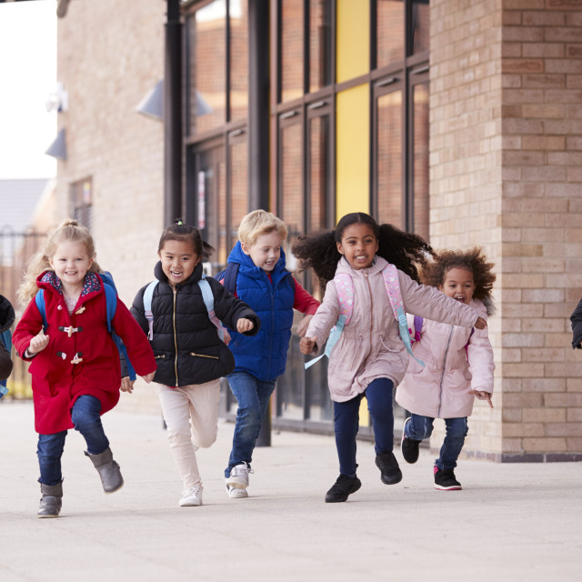 """""""A happy multi-ethnic group of young school kids wearing coats and carrying..."""" stock image"""
