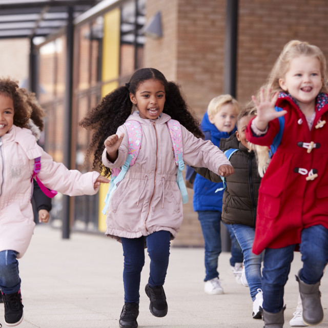 """""""Three happy young school girls wearing coats and carrying schoolbags running..."""" stock image"""