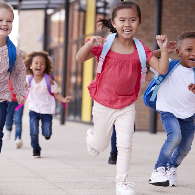 """""""A group of smiling multi-ethnic school kids running in a walkway outside..."""" stock image"""