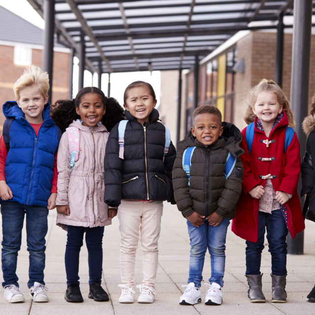 """""""A group of smiling young multi-ethnic school kids wearing coats and carrying..."""" stock image"""