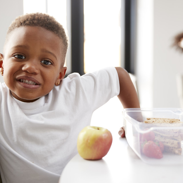 """""""Young black schoolboy sitting at a table smiling in a kindergarten classroom..."""" stock image"""