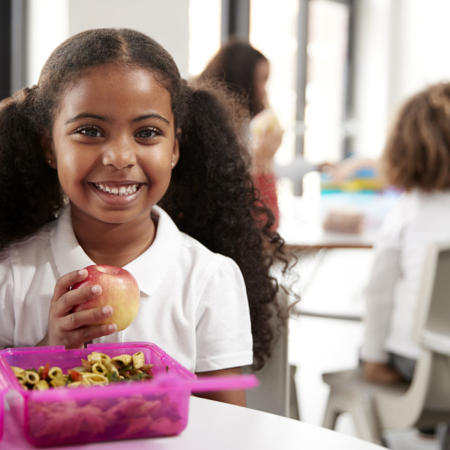 """""""Young black schoolgirl sitting at a table smiling and holding an apple in a..."""" stock image"""