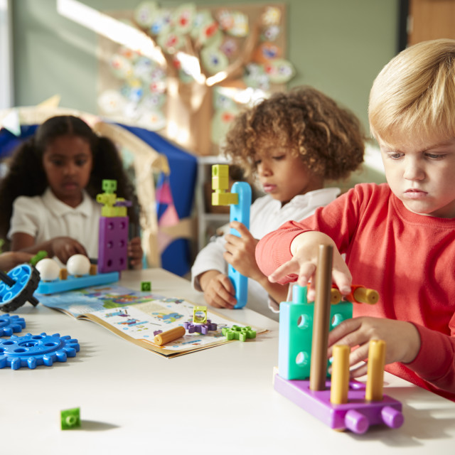 """""""Infant school boy sitting at a table using educational construction toys with..."""" stock image"""