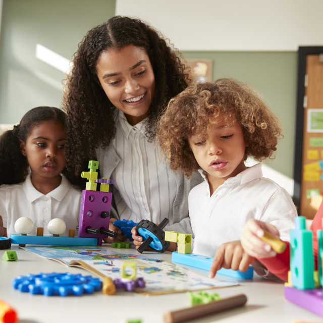 """""""Female teacher sitting at table in play room with three kindergartne children..."""" stock image"""