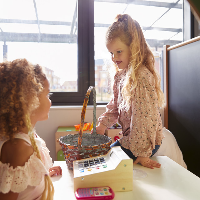"""""""Two young schoolgirls playing shop in a playhouse at an infant school, backlit"""" stock image"""