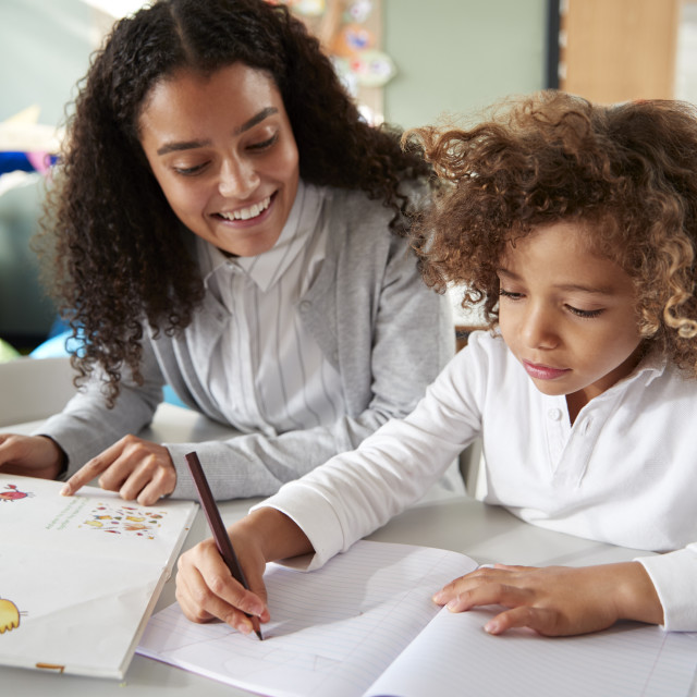 """""""Female infant school teacher working one on one with a young schoolgirl..."""" stock image"""