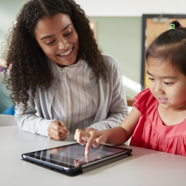 """""""Female infant school teacher working one on one with a Chinese schoolgirl,..."""" stock image"""