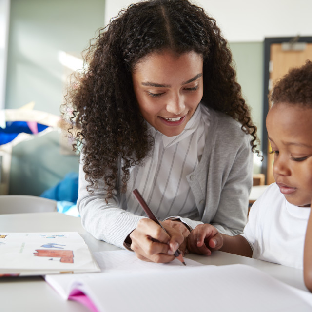 """""""Female infant school teacher working one on one with a young schoolboy,..."""" stock image"""