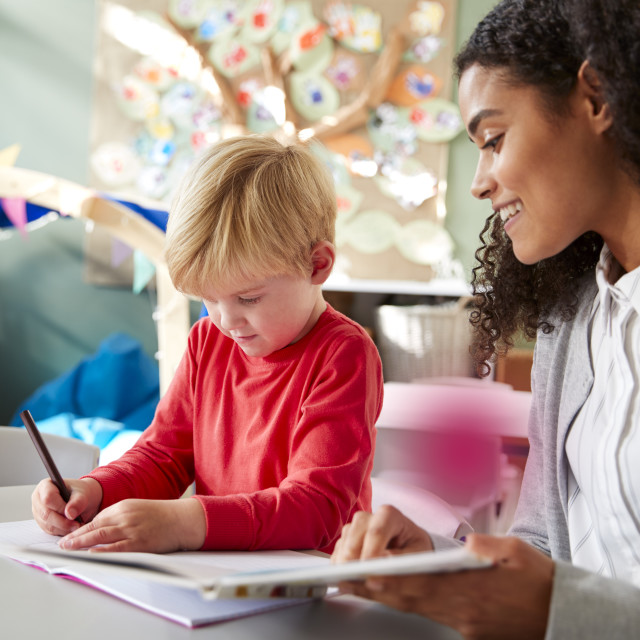 """""""Female infant school teacher working one on one with a young white schoolboy,..."""" stock image"""