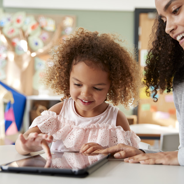 """""""Young mixed race schoolgirl using a tablet computer with a female infant..."""" stock image"""