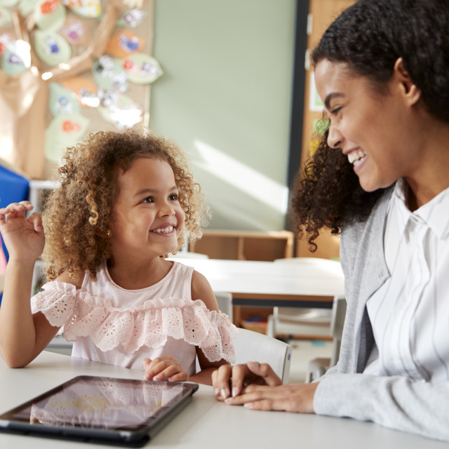 """""""Female infant school teacher working one on one in a classroom using a tablet..."""" stock image"""