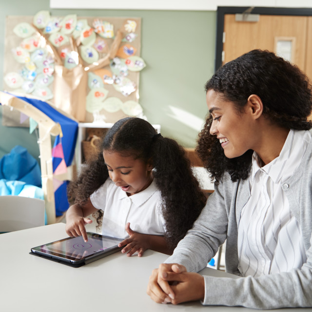 """""""Young black schoolgirl sitting at a table in an infant school classroom using..."""" stock image"""