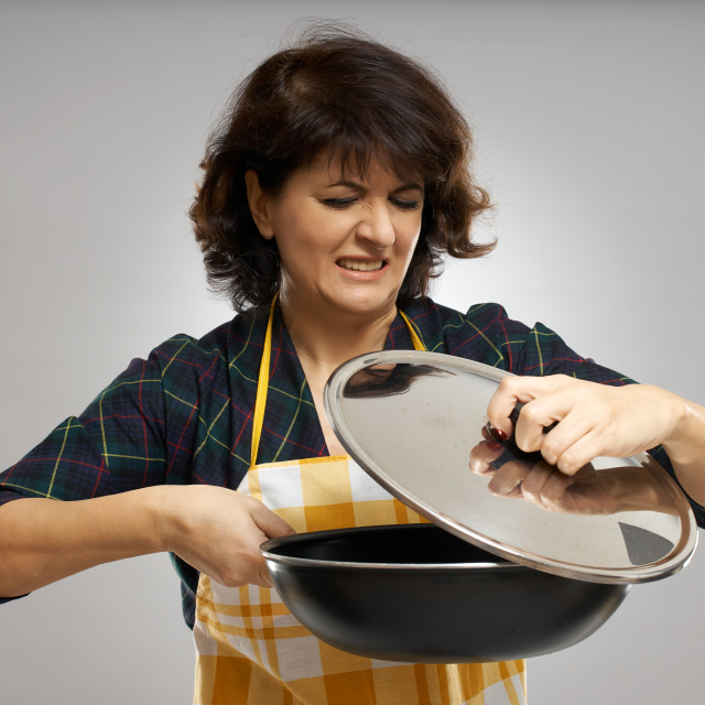 """""""Woman looking in disgust at the content of her pan"""" stock image"""