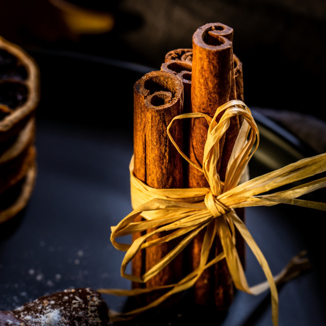 """""""Few cinnamon sticks on black plate with chocolate sweets and dry orange rings"""" stock image"""