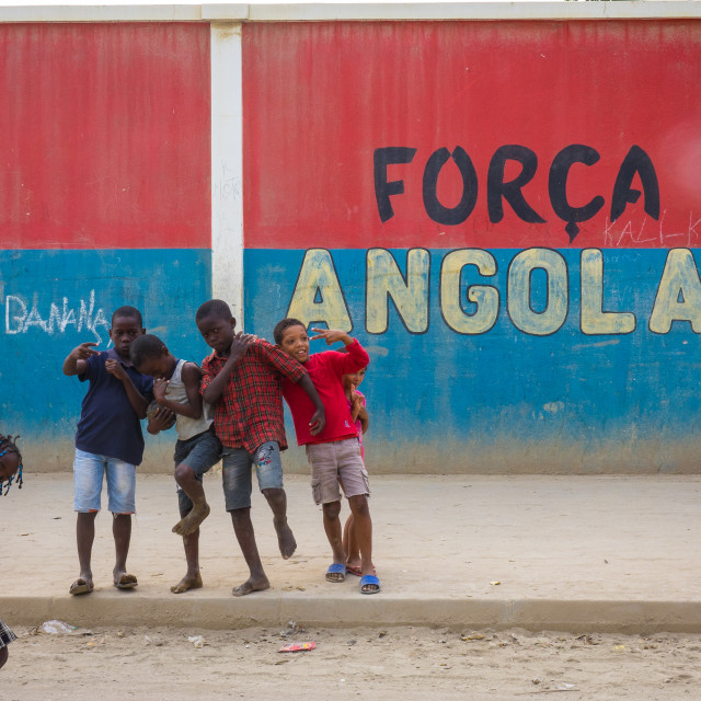 """""""Kids walking in front of a wall with a nationalist slogan, Benguela Province,..."""" stock image"""