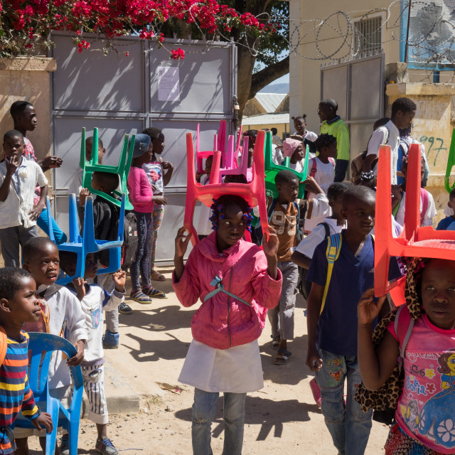 """""""Children going to school with their own chairs, as there are not enough seats..."""" stock image"""