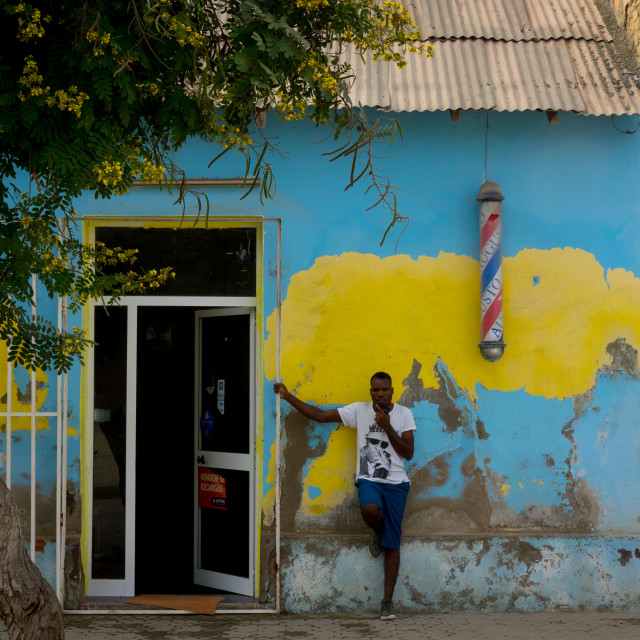 """""""Man standing in front of a barber shop, Benguela Province, Benguela, Angola"""" stock image"""