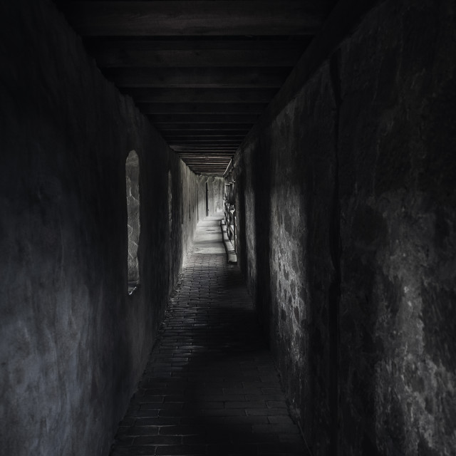 """Ancient corridor with beams of light. Dark hallway in a medieval building."" stock image"