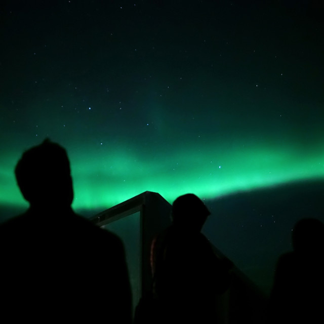 """Silhouette of a man watching the Northern Lights"" stock image"
