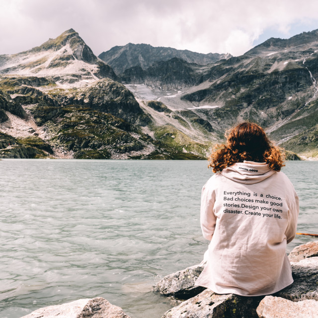 """Young woman sitting at mountain lake in the Alps"" stock image"