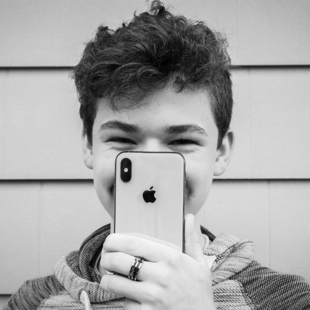 """""""Young teen boy with his iPhone X"""" stock image"""