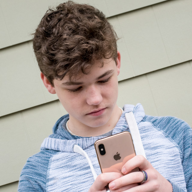 """""""Teenager texting on iPhone"""" stock image"""