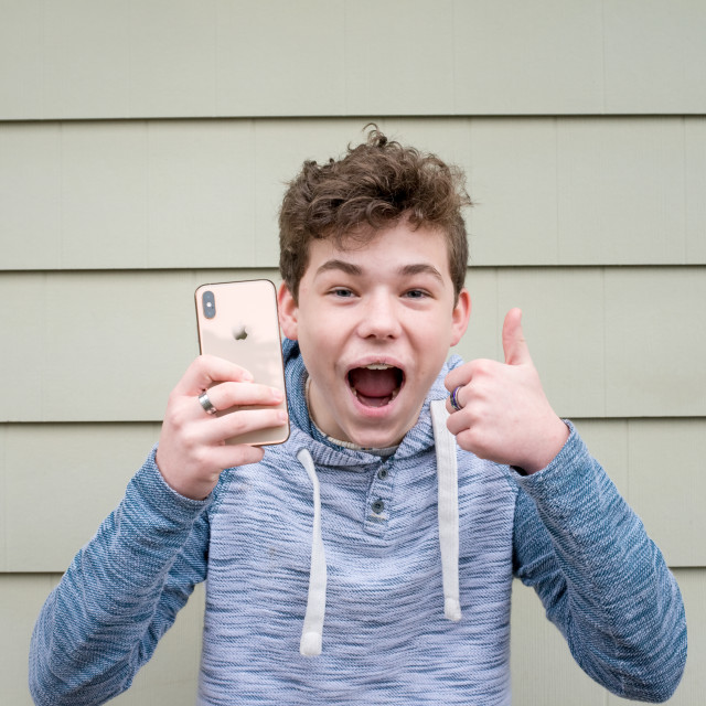 """""""Boy with Apple iPhone thumbs up"""" stock image"""