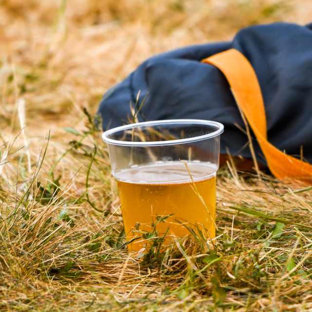 """Disposable plastic cup of beer discarded on the grass"" stock image"