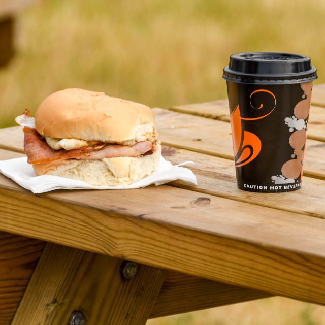 """Hot bacon roll and a cup of coffee on a picnic table"" stock image"