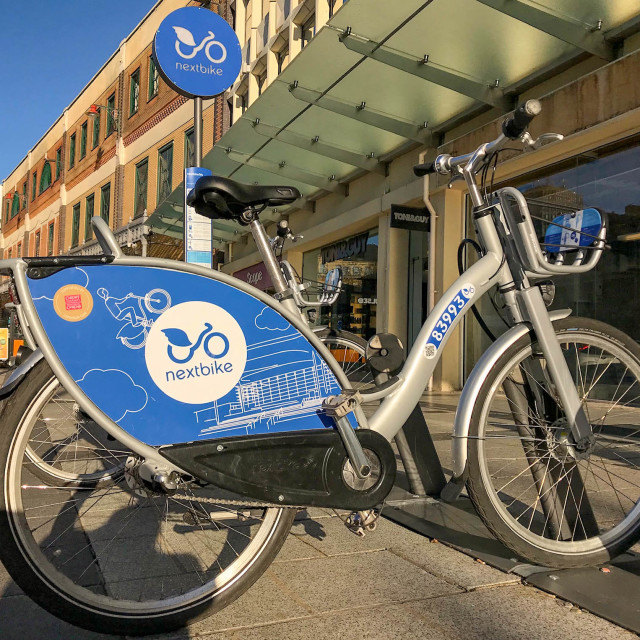"""Bicycle available for hire as part of the ""nextbike"" scheme in Cardiff city centre."" stock image"