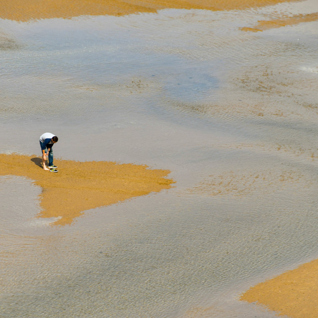 """""""Person on a sandbank cut off by the incoming tide."""" stock image"""