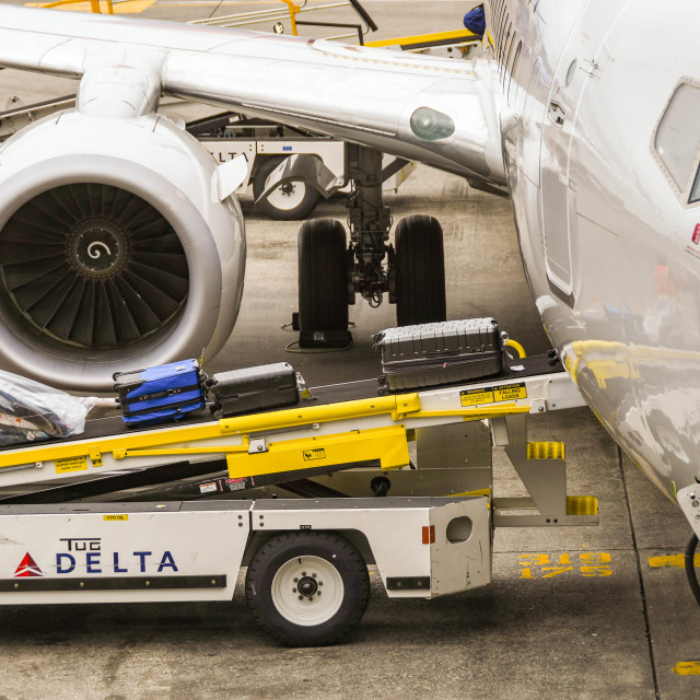 """""""Ground handling equipment loading luggage into a jet"""" stock image"""