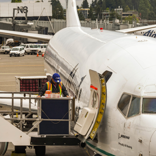 """""""Close up view of an airport worker loading catering supplies into a jet"""" stock image"""