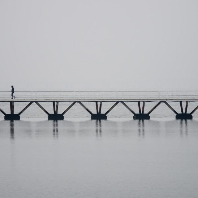 """Lonely man walking on foggy bridge"" stock image"