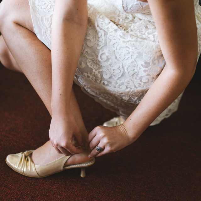 """""""Bride sitting and putting on shoes"""" stock image"""
