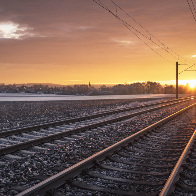 """Railway tracks through frozen nature at sunrise. Traveling context. Winter..."" stock image"