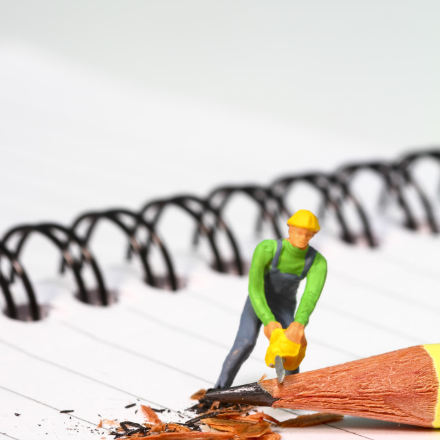 """""""Conceptual diorama image of a miniature figure sharpening a pencil on a note book with copy space"""" stock image"""
