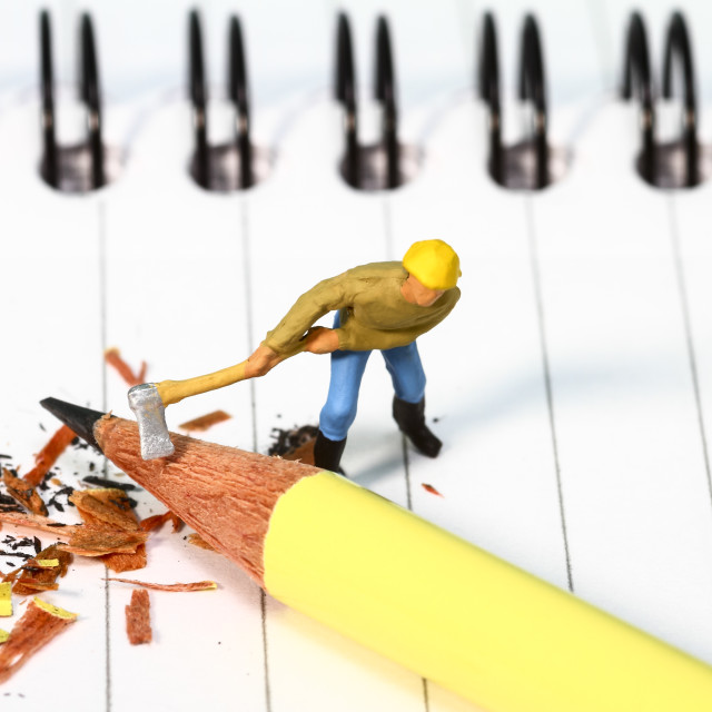 """""""Conceptual diorama image of a miniature figure sharpening a pencil on a note book"""" stock image"""