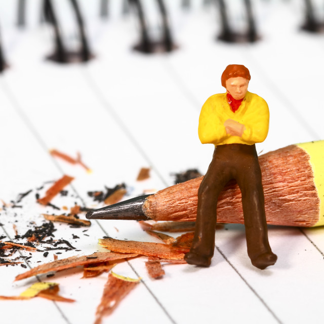 """""""Conceptual diorama image of a miniature figure with writers block sat on a pencil on a note book"""" stock image"""
