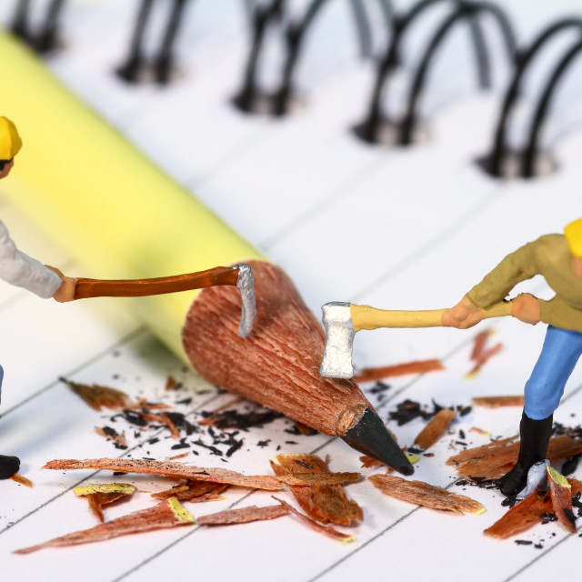 """""""Conceptual diorama image of a miniature figures sharpening a pencil on a note book"""" stock image"""