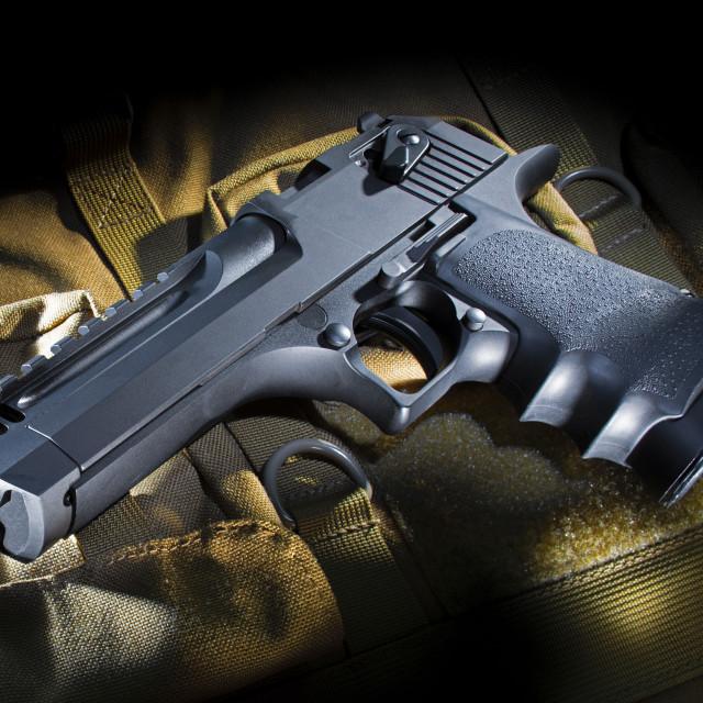 """""""Handgun on a brown nylon bag"""" stock image"""