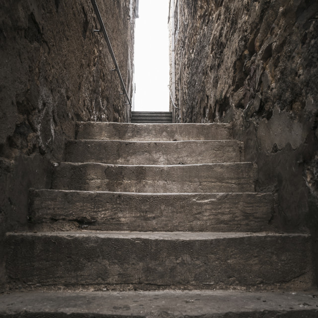 """Narrow stone stairs between buildings. Light at the end of the stairs"" stock image"