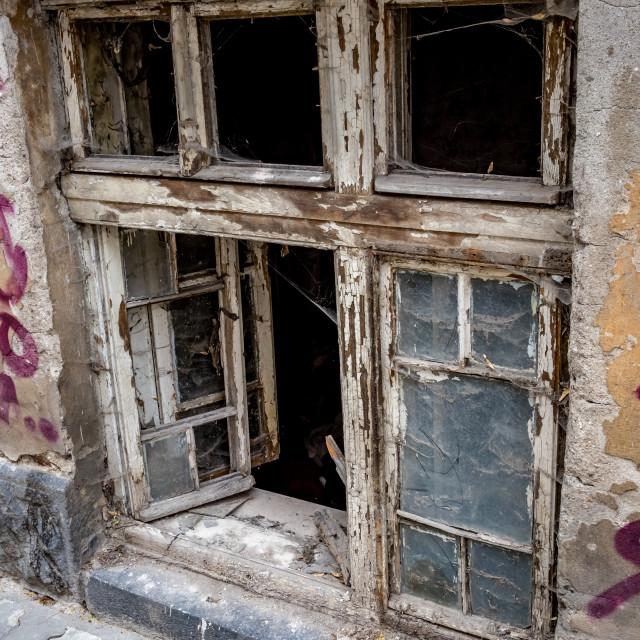 """Open broken wooden window of abandoned house"" stock image"