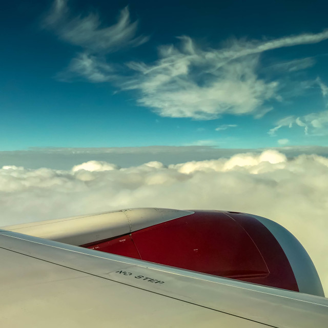"""""""White clouds and blue sky over the wing a Virgin Atlantic aircraft."""" stock image"""