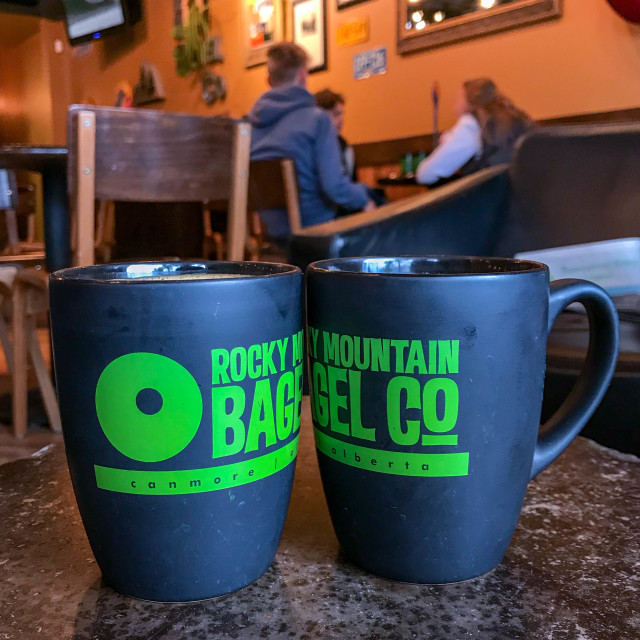 """Two mugs of coffee side by side inside a branch of the Rocky Mountain Bagel Co."" stock image"