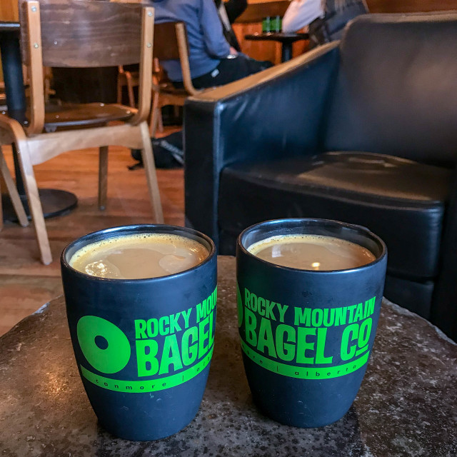 """Two mugs of coffee side by side inside a branch of the Rocky Mountain Bagel Co"" stock image"