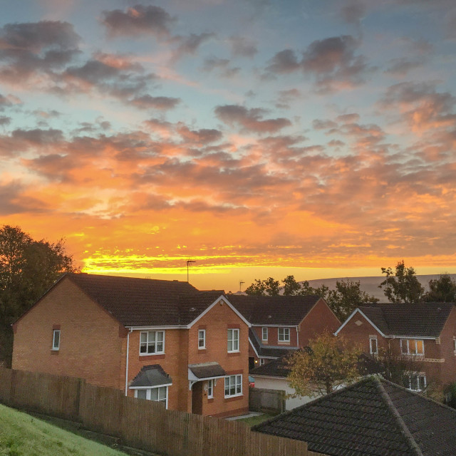 """""""Sunrise and colourful sky above a housing estate"""" stock image"""