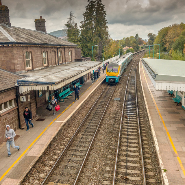 """Train in Abergavenny railway station with passengers walking along the platform"" stock image"