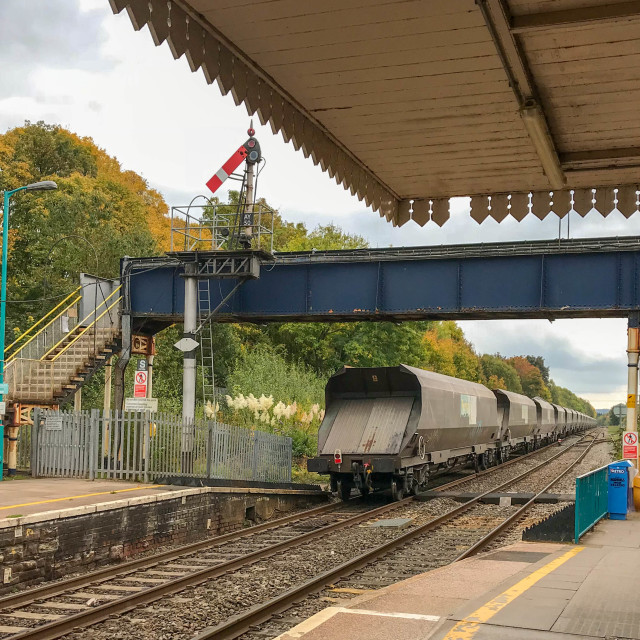 """The last wagon of a goods train passes under the footbridge at Abergavenny railway station."" stock image"